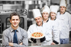 Manager standing in front of chefs holding pizza in kitchen Stock Photography