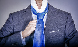 Manager in suit getting dressed. Smart dressed man fixing his tie Royalty Free Stock Photography