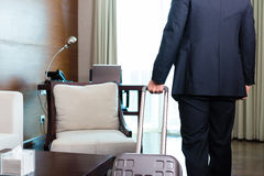 Manager in suit moving into hotel room with his suitcase Royalty Free Stock Photo