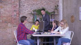 Manager in suit trains new workers in office, business group communication at a table. Manager in suit trains new workers in the office, business group stock video footage