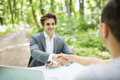 Manager in suit welcomes with handshake at interview new worker man at his office table in green park forest. Business concept. Stock Image