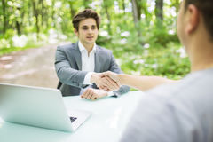 Manager in suit welcomes with handshake at interview new worker man at his office table in green park forest. Business concept. Royalty Free Stock Photo