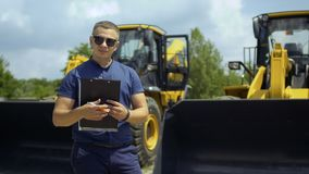 Manager in sunglasses and with folder in hands stand at background of tractors. Young man in sunglasses holding a folder in hand stands at the blurred background stock video