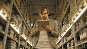 Manager With Tablet PC Checking Goods At Supermarket Warehouse stock video footage