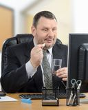Manager takes a pill during e-health doctor appointment. Manager intends to swallow white pill during telehealth doctor appointment. Mature man in black suit Stock Photo