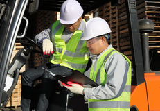 Manager talking with forklift operator. Manager talking to forklift driver in a warehouse Stock Images