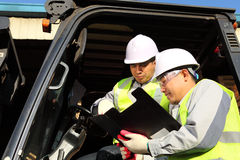 Manager talking to forklift operator. Manager talking with forklift operator on warehouse Royalty Free Stock Images