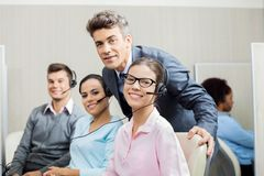 Manager With Team In Call Center. Portrait of confident manager with team in call center Stock Photography