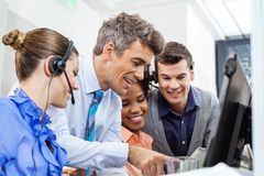 Manager With Team Using Tablet PC In Office Stock Photo