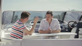 Manager tell buyer about yacht rent. Salesman show yacht to buyer. Young man ask about details of purchase and characteristics of yacht. Businessmen discuss the stock video footage