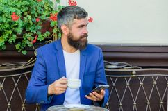 Manager always in touch. Man bearded businessman sit terrace with smartphone and cup of coffee. Take care of business stock photography