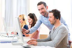 Manager training a young attractive people on computer Royalty Free Stock Photography