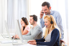 Manager training a young attractive people on computer. View of a Manager training a young attractive people on computer Stock Images