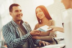 Manager in Travel Agency Giving Tickets To Couple. stock image