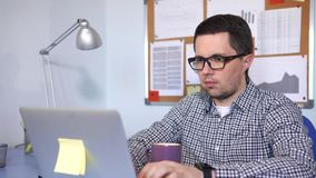 The manager typing text on the laptop sitting at his working place. stock footage
