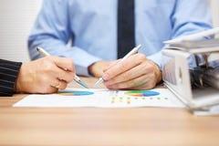 Manager und Geschäftsfrau, die über Verkaufsberichte sich berät Stockbild