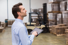 Manager using digital tablet in warehouse. Portrait of male manager using digital tablet in warehouse Royalty Free Stock Images