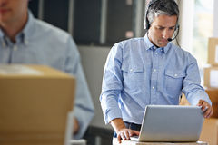 Manager Using Headset In Distribution Warehouse. On Laptop Royalty Free Stock Images