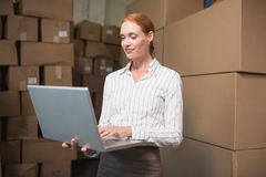 Manager using laptop in warehouse Stock Photo