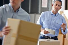 Manager Using Tablet Computer In Distribution Warehouse Stock Photo