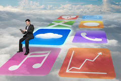 Manager using tablet sitting on shiny app icons with cloudscape Royalty Free Stock Photos