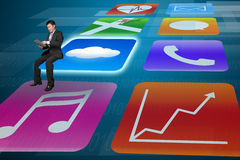 Manager using tablet sitting on shiny app icons tech background Royalty Free Stock Photography