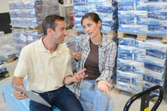 Manager using tablet while talking to worker in warehouse. Co-workers Stock Photography