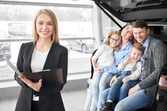 Manager van het autohandel drijven en het gelukkige familie stellen, het glimlachen royalty-vrije stock afbeeldingen