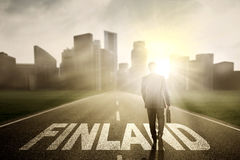 Manager walking above Finland word at sunrise Stock Image
