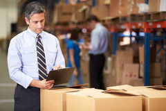 Manager In Warehouse Checking Boxes Royalty Free Stock Image