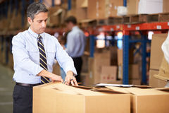 Manager In Warehouse Checking Boxes. Looking at clipboard stock image
