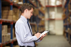Manager In Warehouse With Clipboard. Writing Notes stock photos
