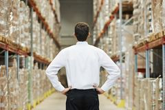 Manager in warehouse. Male manager man standing in big modern warehouse with back towards viewer stock images