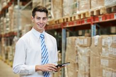 Manager in warehouse. Smiling manager in warehouse with tablet pc computer Stock Photos