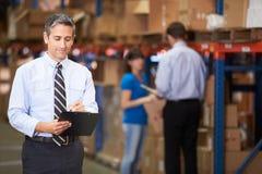 Manager In Warehouse Writing auf Klemmbrett Lizenzfreie Stockfotos
