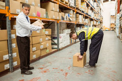Manager watching worker carrying boxes Royalty Free Stock Photography