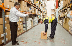 Manager watching worker carrying boxes Stock Photography