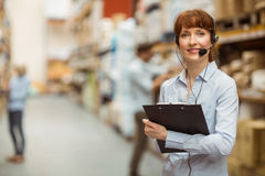 Manager wearing a headset while holding clipboard Royalty Free Stock Photography