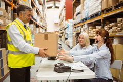 Manager wearing yellow vest giving box to his colleague Royalty Free Stock Image