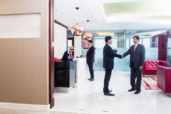 Manager welcoming business associate in office lounge Royalty Free Stock Photo