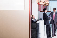 Manager welcoming business associate in office lounge. Indian business executive welcoming Asian associate in office lounge shaking hands Stock Image