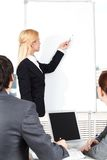 Manager at whiteboard. A women manager showing a whiteboard to her colleagues Royalty Free Stock Photos