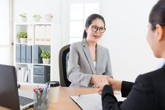 Manager woman handshake with young business sales. Happy smiling office worker manager women handshake with young business sales girl when they reached consensus stock photos