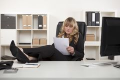 Manager woman relaxing at work reading paper. Manager relaxing at work, with her feet up on the desk as she reads a paper document Royalty Free Stock Image