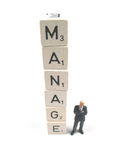 Manager with word spelled out. A manager standing below a tower that spells the word manage stock images