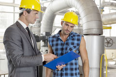 Manager with worker discussing over clipboard in industry Royalty Free Stock Photo