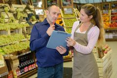 Manager and worker in greengrocers stock photo