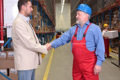 Manager and worker handshake. Manager and older worker hanshake in warehouse,other worker with box in background stock photo