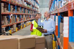 Manager and worker are looking shelves. In a warehouse Royalty Free Stock Photo