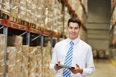 Manager worker in warehouse. Male manager man worker standing in big modern warehouse with tablet computer royalty free stock image